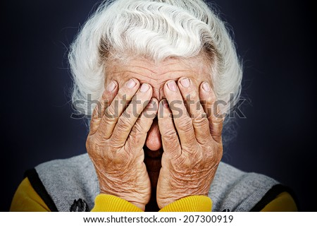 Closeup portrait sad depressed, stressed, thoughtful, senior, old woman, gloomy, worried, covering her face, isolated black background. Human face expressions, emotion, feelings, reaction, attitude - stock photo