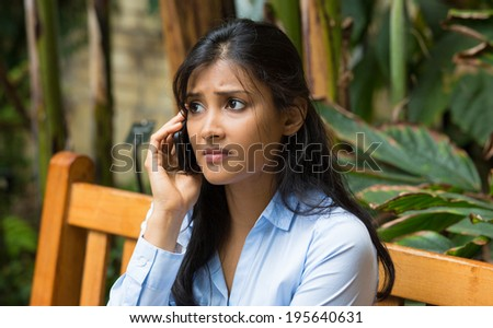 Closeup portrait, sad, depressed, unhappy worried young woman talking on phone, sitting on bench, isolated trees background. Negative human emotions, facial expressions, feelings, reaction. Bad news. - stock photo