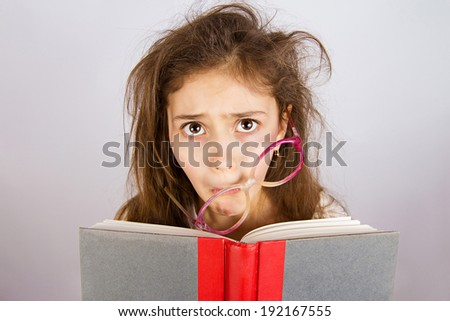 Closeup portrait sad, unhappy, stressed tired, overwhelmed, funny looking little girl with messed up glasses, holding book isolated grey background. Human facial expression, emotion, feeling, attitude - stock photo