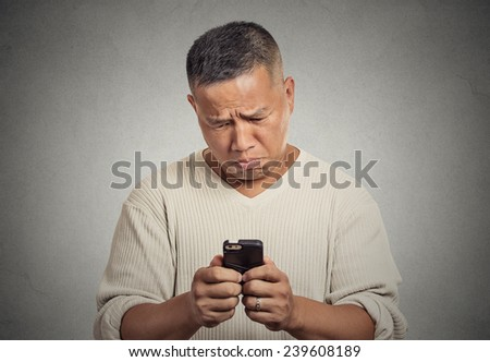 Closeup portrait sad upset middle aged man seeing bad news email text on cellphone, holding smartphone isolated grey wall background. Negative human facial expressions, emotion feeling, reaction - stock photo
