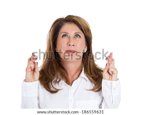 Closeup portrait sad, worried, concerned woman, mother crossing her fingers hoping, asking for best, isolated white background. Human face expressions, emotions, feeling, attitude reaction