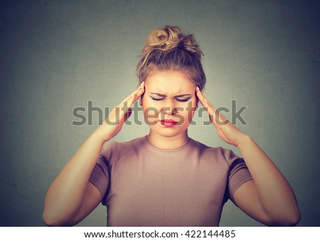 Closeup portrait sad young beautiful woman with worried stressed face expression looking down trying to concentrate isolated on gray wall background  - stock photo