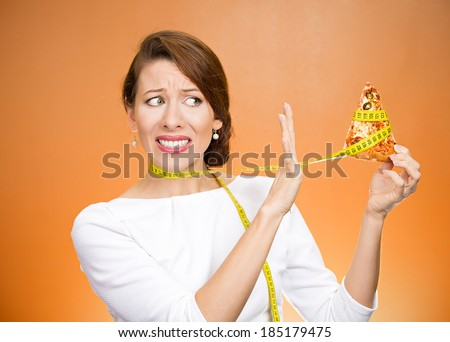 Closeup portrait sad, young, confused woman holding, looking at fatty pizza with measuring tape around, trying to withstand, resist temptation to eat it isolated orange background.  Facial expression - stock photo