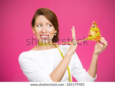 Closeup portrait sad, young, confused woman holding, looking at fatty pizza with measuring tape around, trying to withstand, resist temptation to eat it isolated magenta background.  Facial expression - stock photo