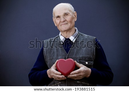 Closeup portrait, senior, elderly, happy man, grandfather holding red heart in hands, looking at you isolated white background. Human emotion, facial expression, reaction. Old people health, longevity - stock photo
