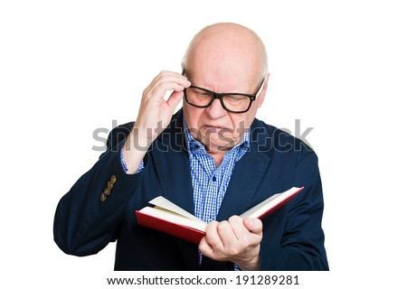 Closeup portrait senior, elderly, mature, annoyed man holding book, glasses having eyesight problems unable to read, isolated white background. Human emotions, facial expressions. Age related changes - stock photo