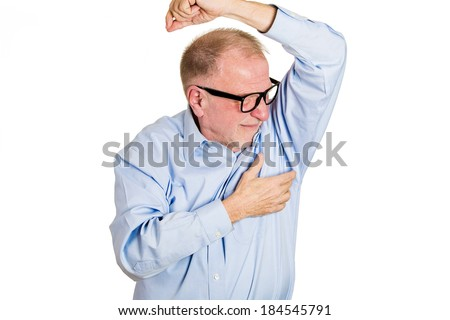 Closeup portrait, senior man, nerd black glasses, sniffing armpit, something stinks, bad, foul odor situation, isolated white background. Negative human emotions, facial expressions, feeling reaction - stock photo
