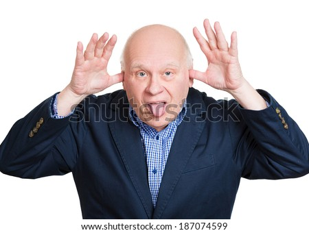 Closeup portrait, senior mature angry man, sticking out tongue at you, thumbs, hands on temple, isolated white background. Negative human emotions, facial expressions, feelings, attitude - stock photo