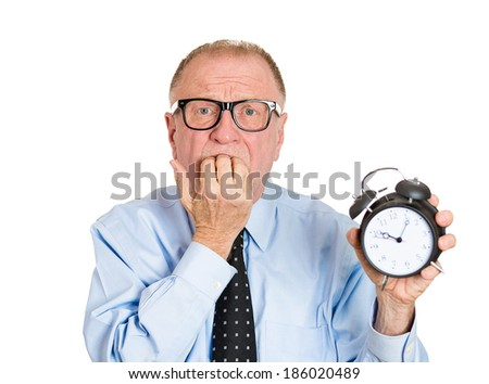 Closeup portrait, senior mature business man, funny worker in black glasses holding clock stressed, running out pressured by lack of time, late for meeting, isolated white background. Negative emotion - stock photo