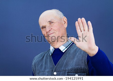 Closeup portrait senior mature grumpy man with bad attitude giving talk to hand gesture with palm outward isolated blue background. Negative emotion facial expression feeling, body language perception - stock photo