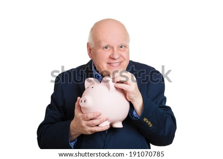 Closeup portrait, senior mature, happy, successful elderly man holding piggy bank making money cash deposit, contribution isolated white background. Clever financial decision, saving, tax free account - stock photo