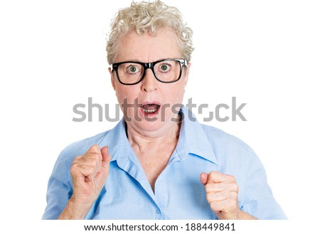 Closeup portrait, senior mature, nerd business woman in black glasses looking shocked, fists in air, isolated white background. Negative human emotions, facial expressions, feelings, reaction - stock photo