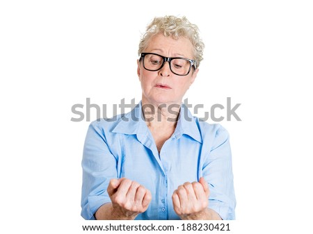 Closeup portrait, senior mature woman in black glasses, obsessive compulsive nerdy, agitated, anxiously staring at fingernails, making sure they clean isolated white background. Face expression - stock photo