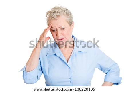 Closeup portrait, senior mature woman in deep, serious thought, daydreaming of problems, looking down, isolated white background. Negative human emotion facial expression feelings.