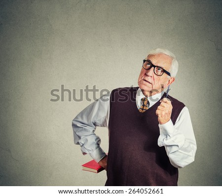 Closeup portrait senior strict teacher holding book and pen, looking up very serious, unhappy and grumpy, isolated gray wall background. Human emotion facial expressions. Education concept - stock photo