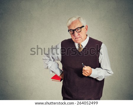 Closeup portrait senior strict teacher holding book and pen, looking very serious, unhappy and grumpy, isolated gray wall background. Human emotion facial expressions. Education concept - stock photo