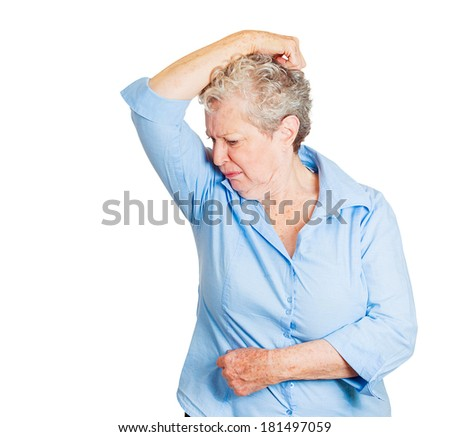 Closeup portrait senior woman, smelling, sniffing her wet armpit, something stinks, very bad, foul odor situation isolated white background. Negative human emotion, facial expression, feeling reaction - stock photo