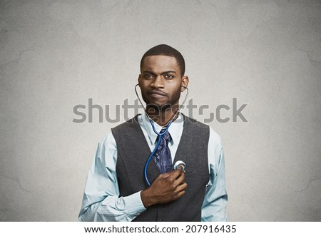 Closeup portrait serious executive man, business person, worker listening to his heart with stethoscope isolated grey background. Preventive medicine, financial condition concept. Face expressions - stock photo
