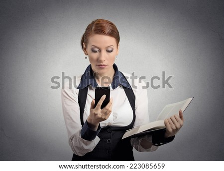 Closeup portrait serious looking business woman company executive reading news on smart phone holding book isolated grey wall background. Human face expression emotion. Phone new technology addiction  - stock photo