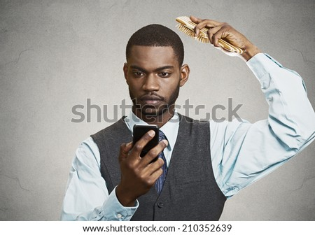 Closeup portrait serious worried business man, corporate executive reading bad news on smart phone holding mobile, combing his hair isolated grey wall background. Human face expressions, emotions - stock photo