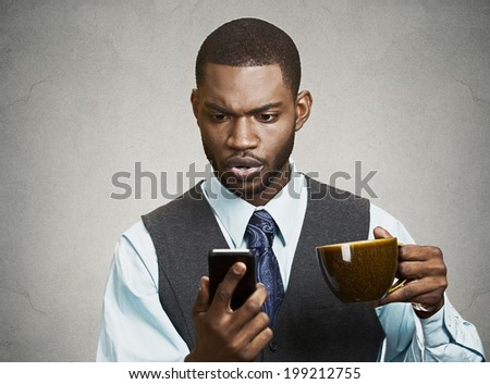 Closeup portrait serious worried business man reading bad news on smart phone holding mobile, drinking cup of coffee isolated black grey background. Human face expression, emotion, corporate executive - stock photo