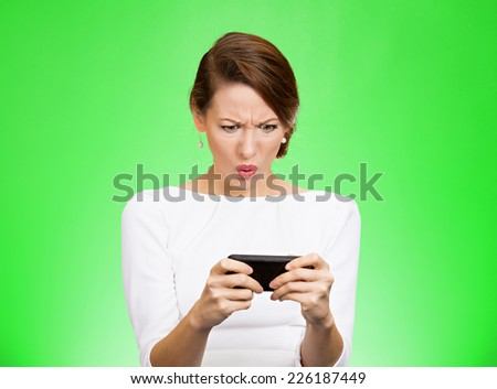 Closeup portrait serious worried business woman reading bad news on smart phone holding mobile looking displeased isolated on green background. Human face expression, emotions feelings - stock photo