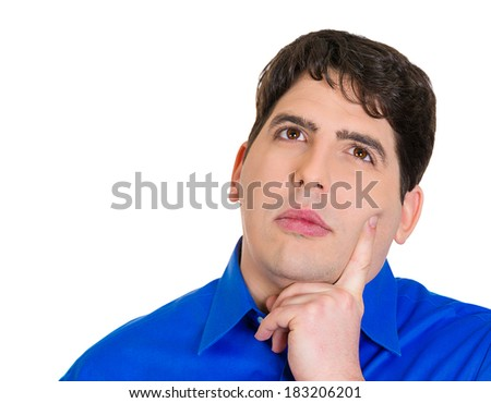 Closeup portrait serious young man thinking, daydreaming deeply, bothered by something, finger on cheek, looking upwards, isolated white background. Negative human emotions, facial expression feeling