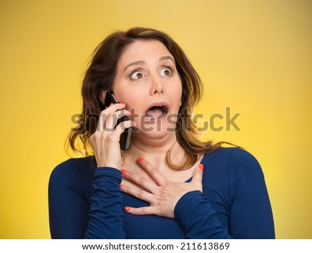 Closeup portrait shocked business woman, employee talking on cell phone having unpleasant conversation, receiving shocking news isolated yellow background. Negative emotion facial expression reaction - stock photo