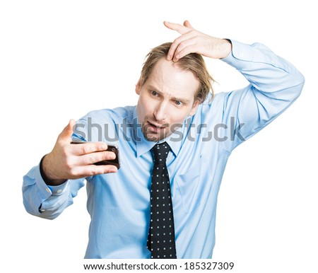 Closeup portrait, shocked man feeling head, surprised he is losing hair, receding hairline or seeing bad news on cellphone, isolated white background. Negative facial expressions, emotion feeling - stock photo