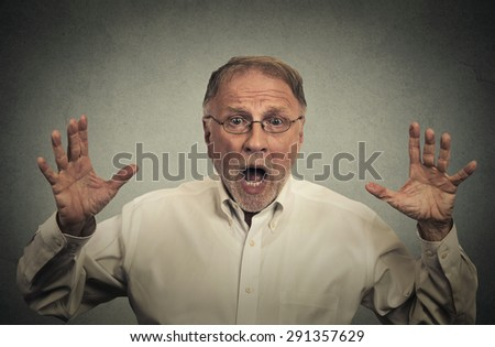Closeup portrait shocked stunned surprised man eyes and mouth wide open, hands in air yelling screaming isolated on gray wall background. Negative human emotion facial expression feeling - stock photo