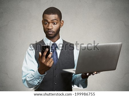 Closeup portrait shocked, surprised business man reading bad news on smart, mobile, cell phone holding laptop computer isolated black grey background. Human face expression emotion corporate executive - stock photo
