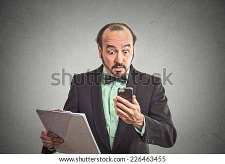 Closeup portrait shocked surprised business man reading bad news on smart, mobile, cell phone holding clipboard isolated grey wall office background. Human face expression emotion corporate executive - stock photo