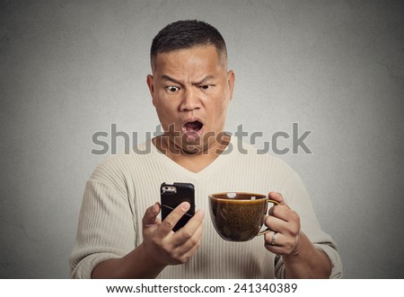 Closeup portrait shocked surprised middle aged man with wide open mouth reading breaking news on smart phone, holding cup of coffee isolated grey wall background. Human face expression emotion - stock photo