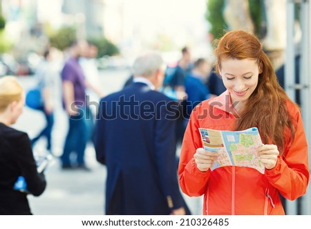 Closeup portrait, shot of beautiful Traveling young Woman reading a Map, isolated busy city street background. Travel life style concept. San Francisco California USA. Positive face expression - stock photo