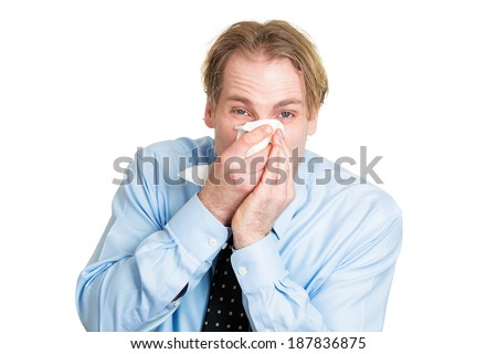 Closeup portrait sick, ill young business man, student, worker, allergy, germs cold, blowing his nose with kleenex, looking miserable, unwell, very sick isolated white background. Flu season, vaccine - stock photo