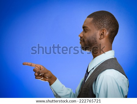 Closeup portrait side view profile young smiling handsome man pointing at you with index finger isolated blue background. Human emotion facial expression feeling sign symbol body language. Pick target - stock photo
