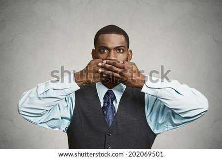 Closeup portrait, silent young business man covering closed mouth observing. Speak no evil concept, isolated black background. Negative human emotion, facial expression sign symbol. Media news coverup - stock photo