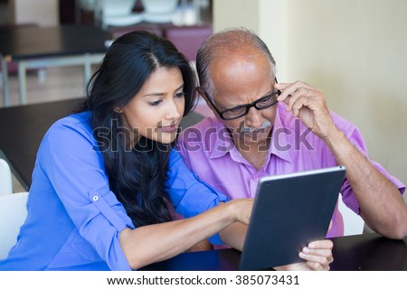 Closeup portrait, sitting young woman showing elderly with black glasses to use portable device,scrutinizing data with great concern, isolated indoors background - stock photo