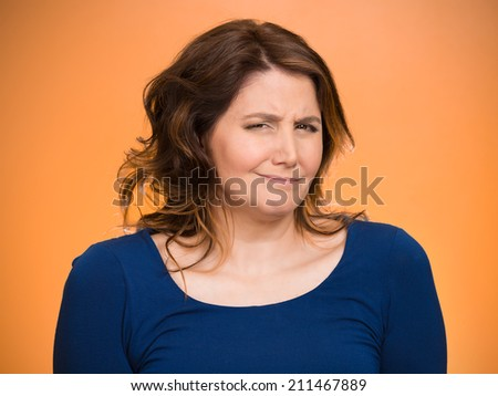 Closeup portrait skeptical young woman looking suspicious, some disgust on her face mixed with disapproval isolated orange background. Negative human emotion, facial expression, feeling, body language - stock photo