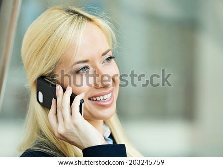 Closeup portrait, smiling attractive successful businesswoman, entrepreneur, corporate employee talking on cellphone, walking in company building, isolated background office windows. Positive emotion - stock photo