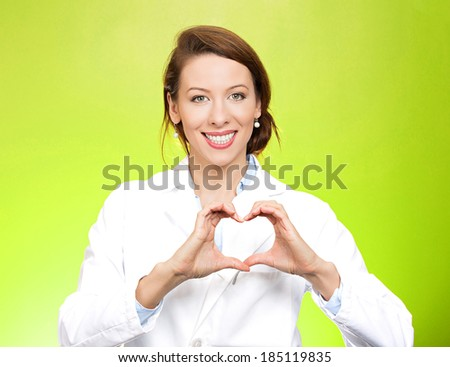 Closeup portrait smiling, cheerful health care professional, pharmacist, dentist, nurse making heart sign with hands, isolated green background. Positive human emotions, facial expressions, feelings - stock photo