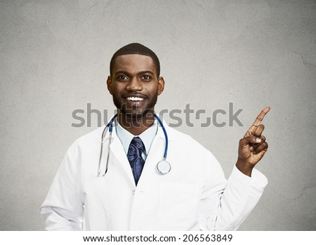 Closeup portrait smiling, happy doctor, pharmacist, dentist pointing with finger at copy space ready for advertisement isolated black background. Positive face expression, emotions, feeling, attitude - stock photo