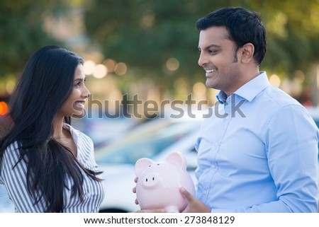 Closeup portrait, smiling happy man in blue shirt and woman holding piggy bank, isolated outdoors background with car and trees. Smart financial investments and advice - stock photo