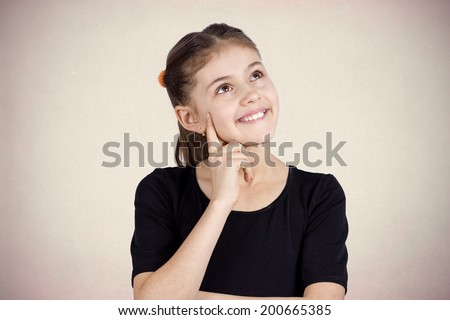 Closeup portrait, smiling, happy pensive little girl touching her cheek, thinking, daydreaming about something, looking up isolated grey background. Human face expressions, emotions, reaction feelings - stock photo