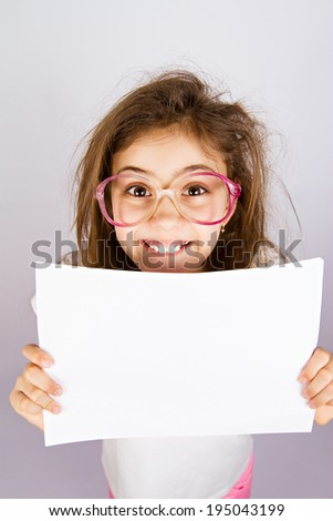 Closeup portrait smiling little, cute, funny looking girl with glasses holding blank piece of white paper isolated grey background. Positive human emotion, facial expression, reaction. Life perception - stock photo