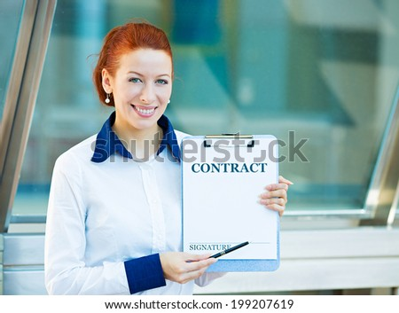 Closeup portrait smiling young business woman, company employee holding contract document pointing with pen at space for signature isolated corporate office background Positive face expression emotion - stock photo