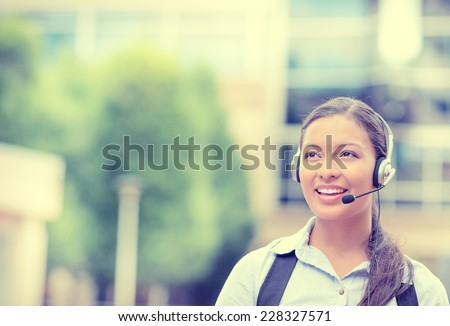 Closeup portrait smiling young female customer service representative, call center agent, support staff, operator with phone headset isolated on background with trees, city buildings. Face expression - stock photo