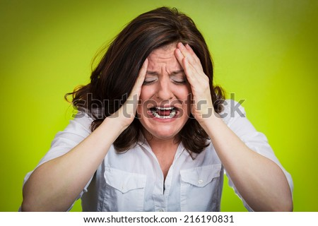 Closeup portrait stressed business woman having breakdown hysterical yelling screaming with temper tantrum isolated green background. Negative human emotions facial expressions reaction attitude