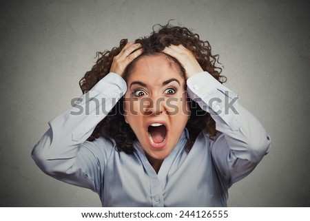 Closeup portrait stressed, frustrated shocked business woman pulling hair out yelling screaming temper tantrum isolated grey wall background. Negative human emotion facial expression reaction attitude - stock photo