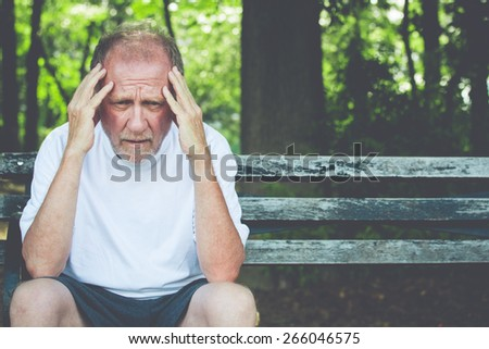 Closeup portrait, stressed older man in white shirt, hands on head with bad headache, sitting on bench, isolated background of trees outside. - stock photo